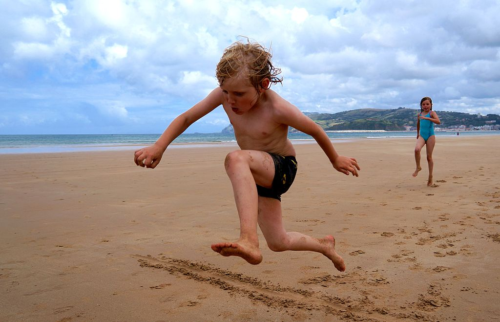 boy's long jump at the beach